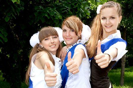three funny graduates posing outdoors photo