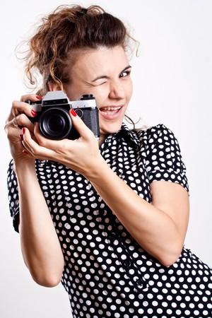 beautiful woman in a black polka dot dress with camera photo