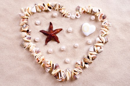 seashells in sand in the form of heart