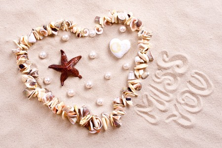 love you: seashells in sand in the form of heart with text