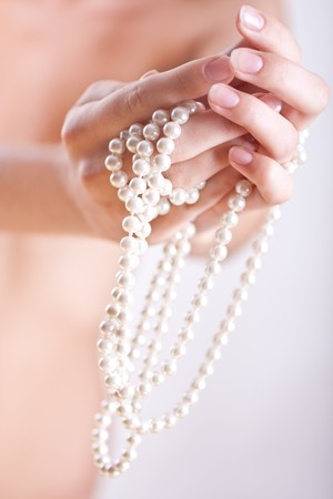 ornament of pearls in the womens hands Stock Photo