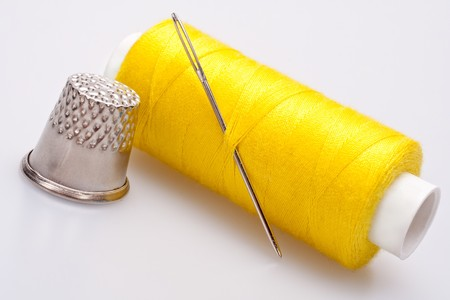 spool of thread for sewing with needle and thimble