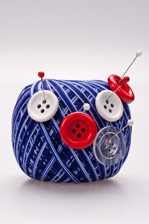 red and white pins in wool ball with buttons