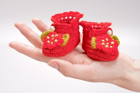 crocheted booties for a girl in the woman hand photo