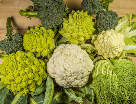 varieties of vegetables: green savoy cabbage, broccoli, cauliflower and white roman