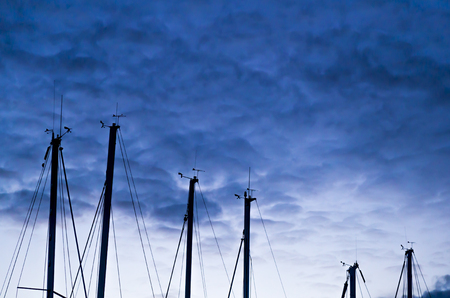 masters boat mast silhouetted against the cloudy sky