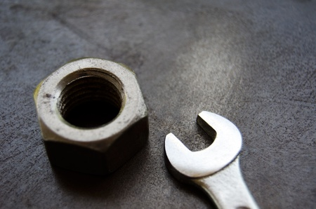 Nut and spanner on metal workbench background photo