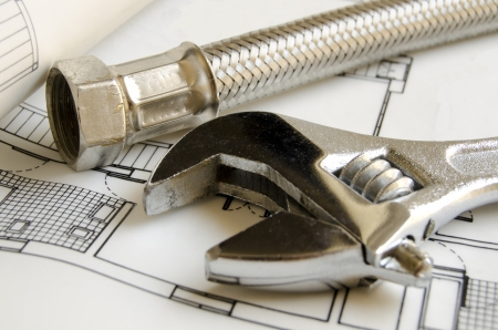 spanners: Plumbing tools on house blueprint Stock Photo