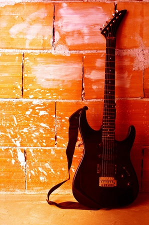 Electric guitar on old wall with copyspace photo