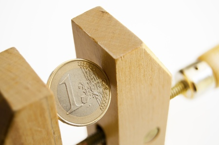 euro screw: Euro coin under pressure in  a wooden clamp