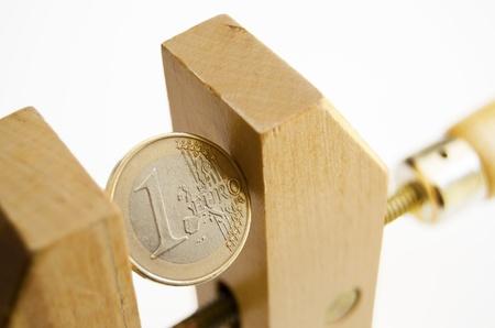 under pressure: Euro coin under pressure in  a wooden clamp