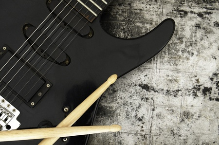 Electric guitar and drumsticks on a grunge background