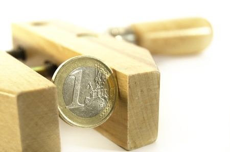 euro screw: Euro coin in a wooden clamp - crisis concept