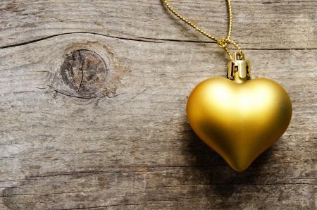 Golden heart over an aged wooden background