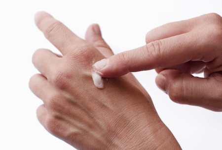 Female hands applying lotion over hand skin