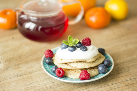 Homemade pancakes with fruits and fresh oranges and lemons on the background