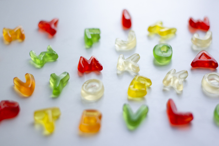 Shiny gummy alphabet letters on white background