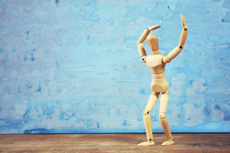 Wooden model showing dramatical pose in front of blue art background