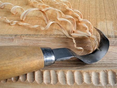 tallado en madera: Primer plano de un cuchillo de gancho tallado y virutas de madera Foto de archivo