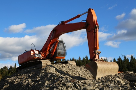 Excavator in quarry on sunny autumn day Stock Photo