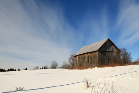 Old abandoned barn in a field on a bright winter morning.