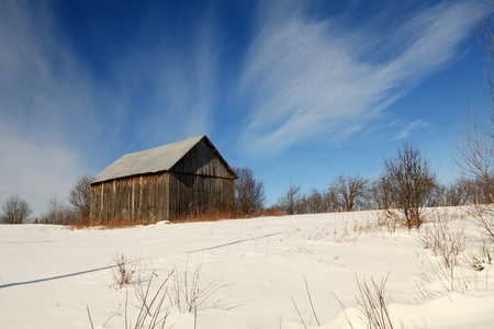 old barn in winter: Beautiful winter morning in a field located in Quebec, Canada. Stock Photo