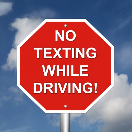 no cell phone: No Texting While Driving Sign mounted on a pole with sky background. Stock Photo