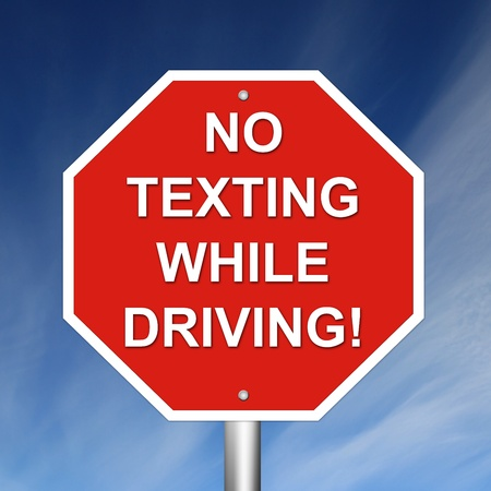no cell phone: No Texting While Driving Sign mounted on pole with sky background. Stock Photo