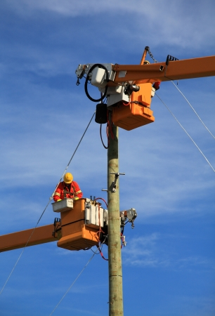 Two electrical technicians connecting power to a new construction