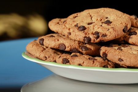 Plate of chocolate chip cookies on glass table photo
