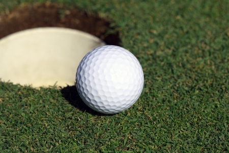 A golf ball stops on the edge of the cup