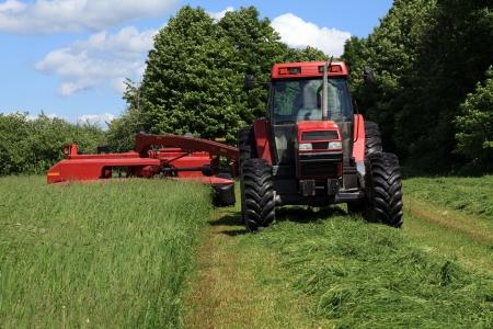 gras maaien: Tractor pulling haymower in een veld gelegen in Quebec, Canada