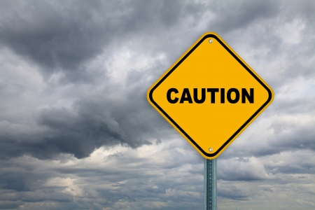 be careful: Yellow caution road sign on cloudy sky background