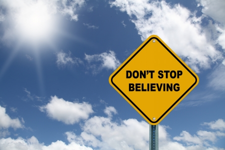 believing: Yellow don t stop believing road sign on a blue sky