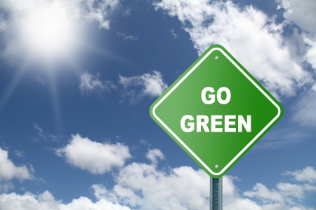 Go green road sign on a sky background photo