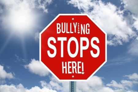 threat of violence: Red bullying stops here stop sign on sky background
