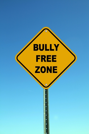 kick out: Yellow bully free zone road sign on bright blue sky background Stock Photo