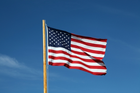 American flag waving in the wind against of beautiful blue sky photo