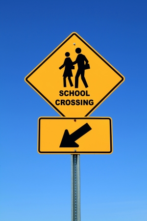 post secondary schools: School crossing sign against blue sky Stock Photo