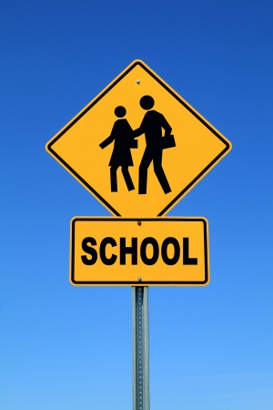zone: Gele schoolbus crossing sign tegen de blauwe hemel