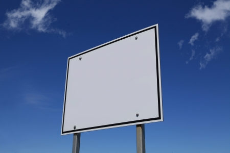 Blank white sign against blue sky with white clouds photo