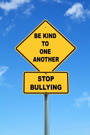 Yellow be kind to one another stop bullying road sign photo