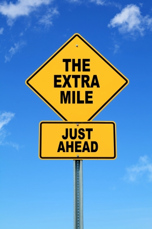 mile: Yellow motivational road sign the extra mile just ahead Stock Photo