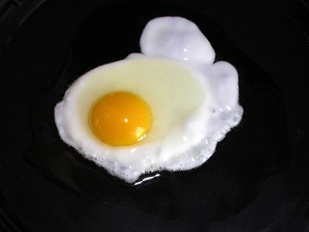 exuberance: An egg is being cooked in a pan