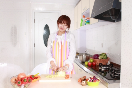 20 25: A Chinese woman is cooking on a chopping block with various kinds vegetable