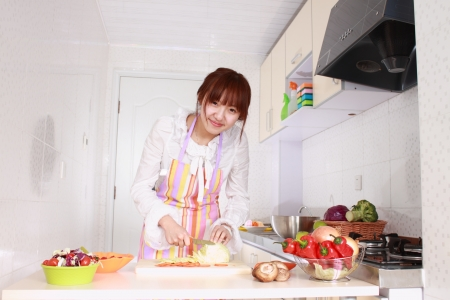 A Chinese woman is cooking on a chopping block with various kinds vegetable