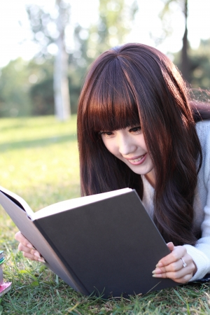 Studying happy young woman reading her book
