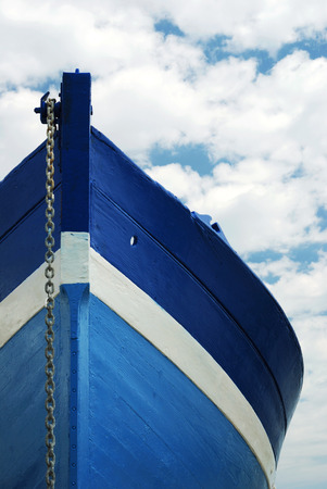 nautical vessels: Front view of a wooden white and blue row fisherman boat under a cloudy sky