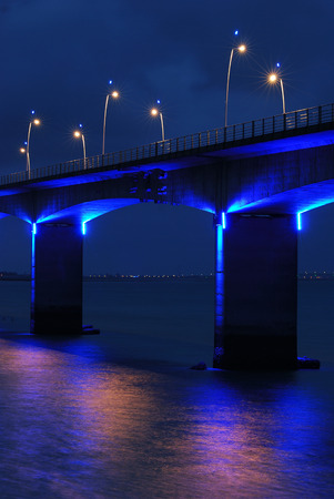 Part of a brightly Illuminated Viaduct under dark cloudy sky  Stock Photo