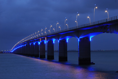 Brightly Illuminated Viaduct under dark cloudy sky  photo